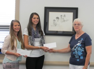 Dr. Eleanor Wright, Caswell Center Foundation Vice Chairperson (R) presents Alexandria Ivey and Lindsay Warren each a $1000 scholarship check.